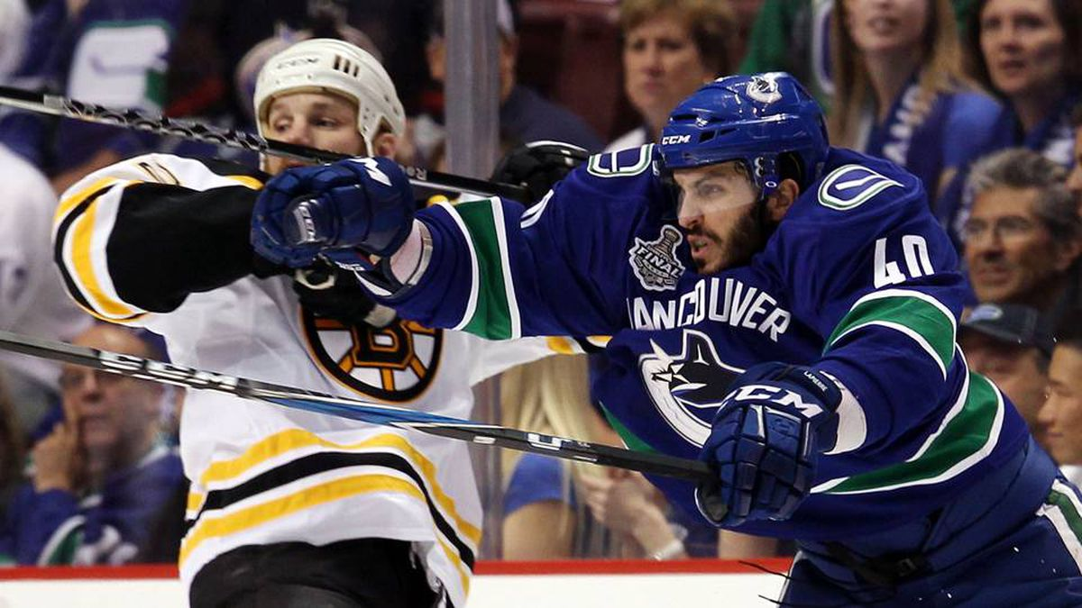 Shawn Thornton of the Boston Bruins draws contact against Maxim Lapierre of the Vancouver Canucks during the first period.