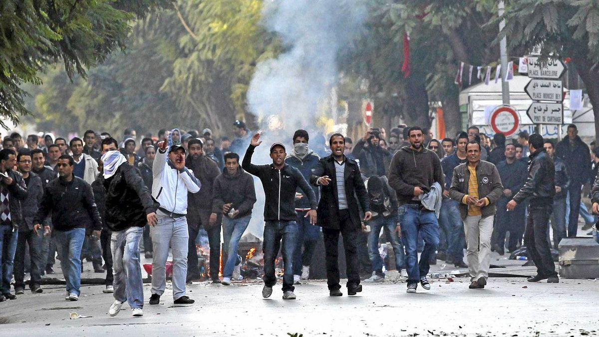 Demonstrators face police during clashes in Tunis, Friday, Jan. 14, 2011. Tunisia's president declared a state of emergency and announced that he would fire his government as violent protests escalated Friday, with gunfire echoing in the North African country's usually calm capital and police lobbing tear gas at protesters.