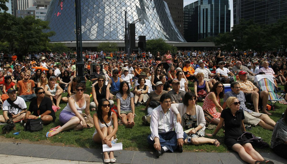 People watch the state funeral of former NDP leader Jack Layton outside the Roy Thomson Hall, Toronto.