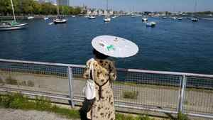 A woman hides from the sun under a parasol on the Toronto waterfront during an extreme heat alert for the city on May 24, 2010.