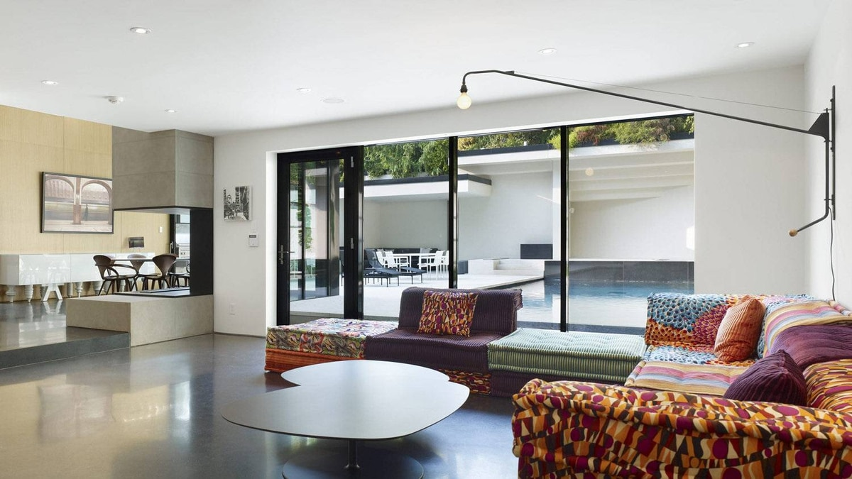 """The family room looking to breakfast room. Since the family room has no basement underneath, it's thought that it was originally Lawren Harris's garage. It features a wild, colourful sofa by Missoni: """"No other colour, we got it with that,"""" jokes Mr. Mandel."""