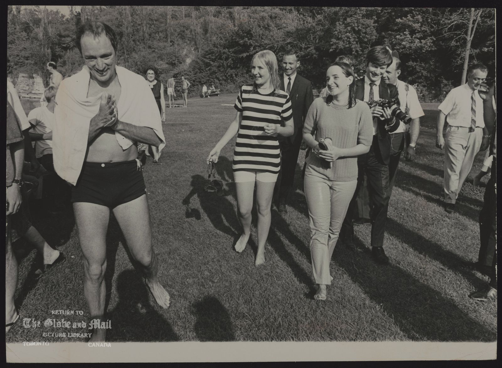 Pierre Elliott TRUDEAU Quebec. Politician Emerging from swim, Prime Minister Trudeau walks with his Stratford friends Ann and Mary, followed by newsman and photographers. [Ann Hayes, 15, striped sweater, and Mary Pinkney,15, solid-colour sweater]