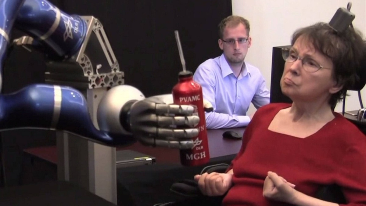 In a clinical trial, a woman used the BrainGate system to mentally control a robotic arm and reach for a drink.