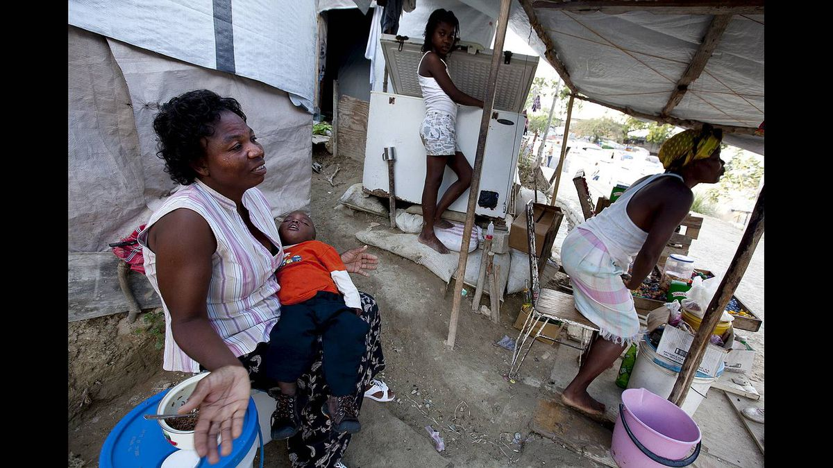 Merit St. Fleur, 34, holding her two-year-old son, near her tent at the Pentionvile Golf Course Camp for Displaced Persons in Port-au-Prince, Haiti.