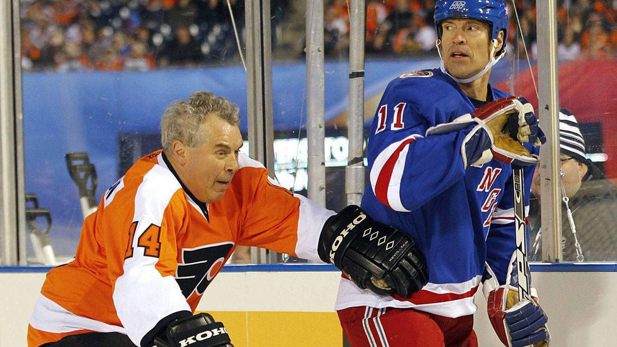 Joe Watson, left, of the Philadelphia Flyers alumni team, checks Mark Messier, of the New York Rangers alumni team. (AP Photo/Tom Mihalek)