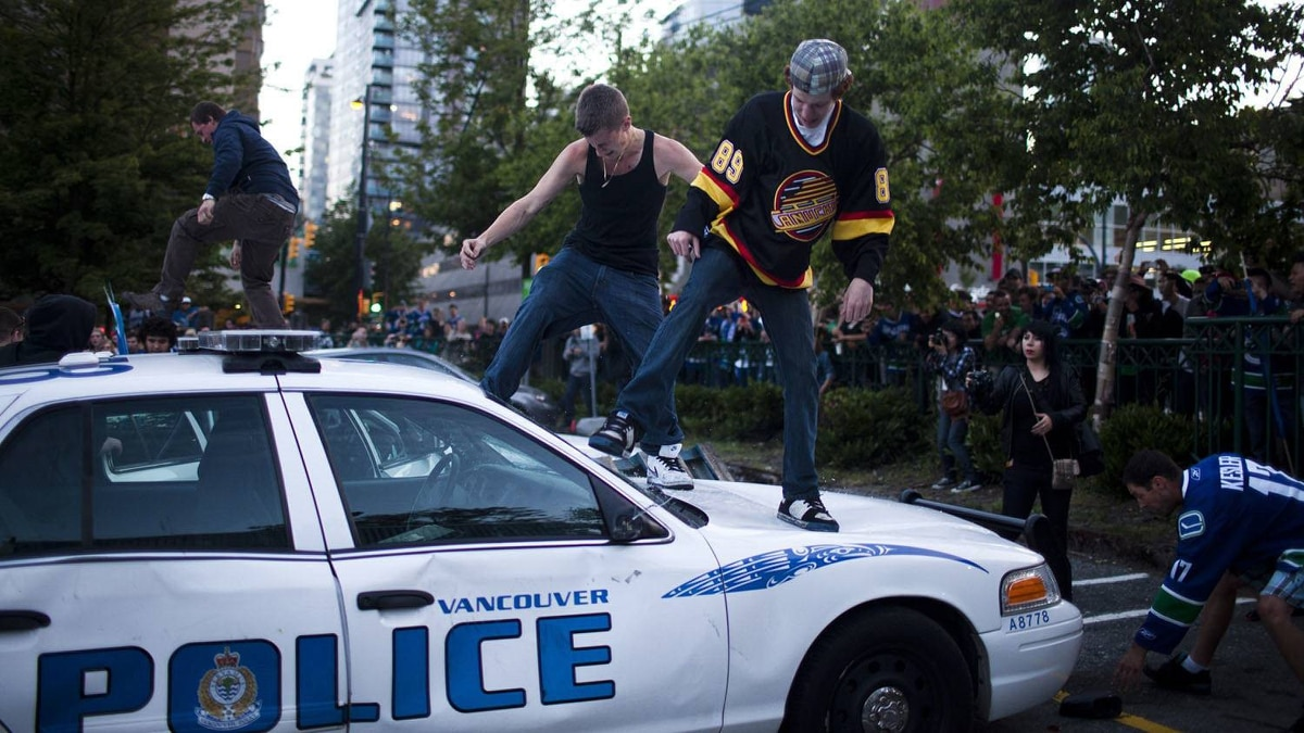Rioters kick in the windshield of a police cruiser at the corner of Cambie Street and Georgia Street in Vancouver after the Boston Bruins beat the Canucks to win the Stanley Cup.