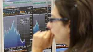 A trader checks monitors at a bank, in Milan, Italy, Monday, Aug. 8, 2011.