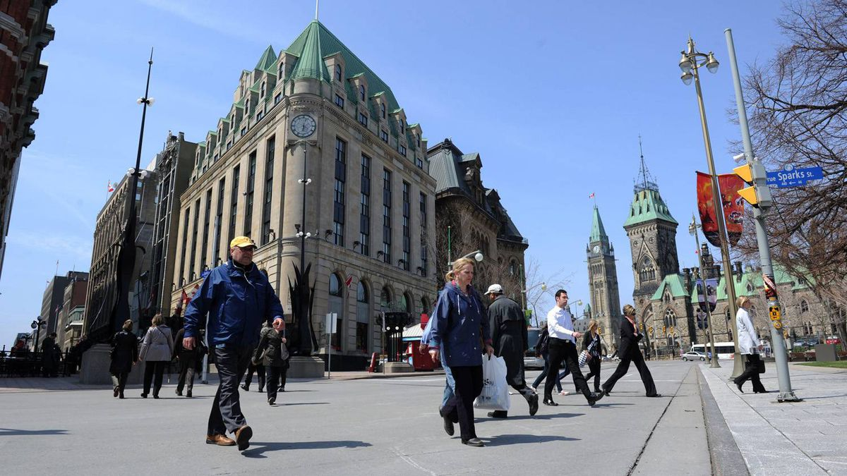 Pedestrians cross Elgin Street in view of the Peace Tower on Parliament Hill.