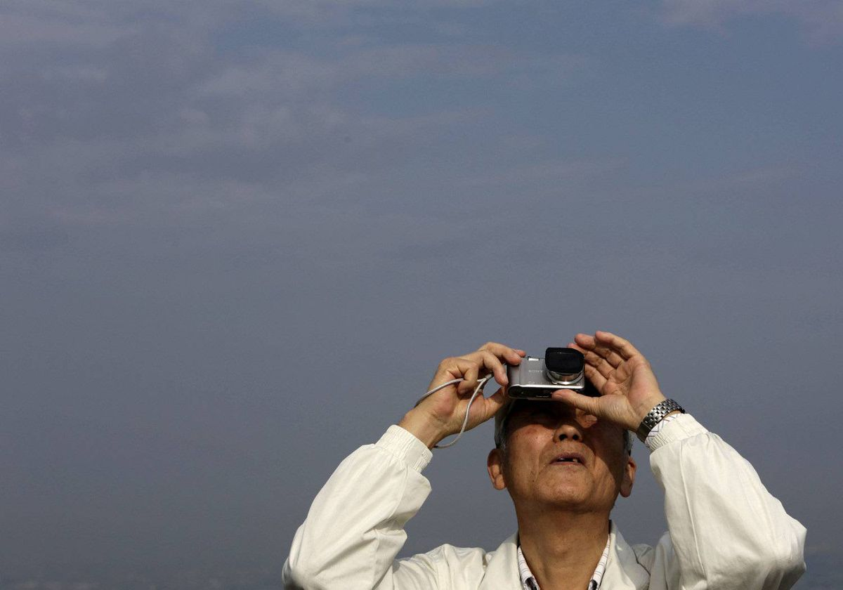 A man takes photos of an annual solar eclipse at a rooftop of the Roppongi Hills complex in Tokyo May 21, 2012.