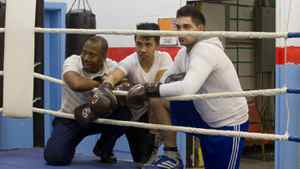 Montreal police officer Evens Guercy (left) watches training alongside 17- year old Alexandre Leng (centre) by the ring at Guercy's Hope Boxing Club in the St. Michel district of Montreal, March 19, 2012.