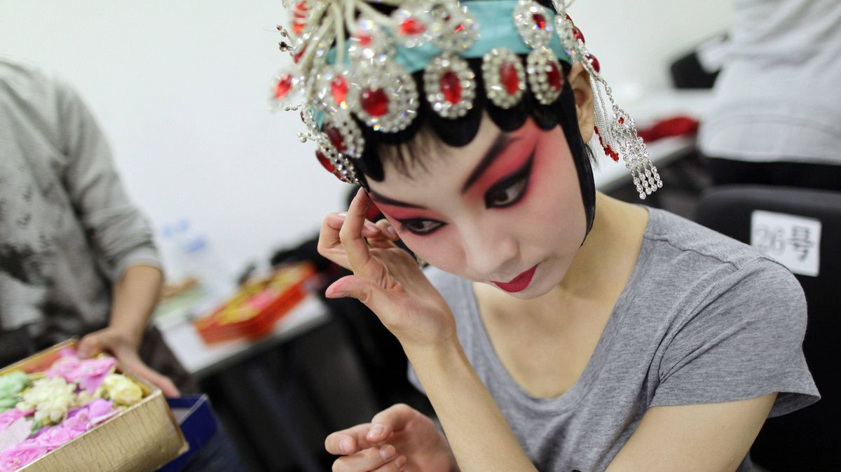 A performer puts on her make-up before a Beijing opera performance for the closing ceremony of the first young Beijing Opera Actors' Arena contest in Beijing, September 16, 2011.