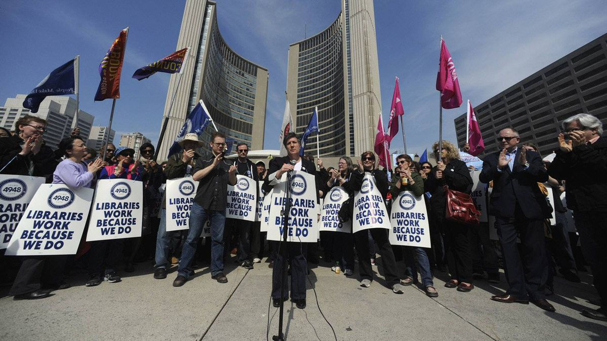 Maureen O'Reilly (centre behind microphone), president of CUPE Local 4948, addresses Toronto public library workers gathered outside City Hall on March 19, 2012. Toronto's 2,300 library employees walked off the job after 5 p.m. Sunday, shuttering 98 branches across the city.