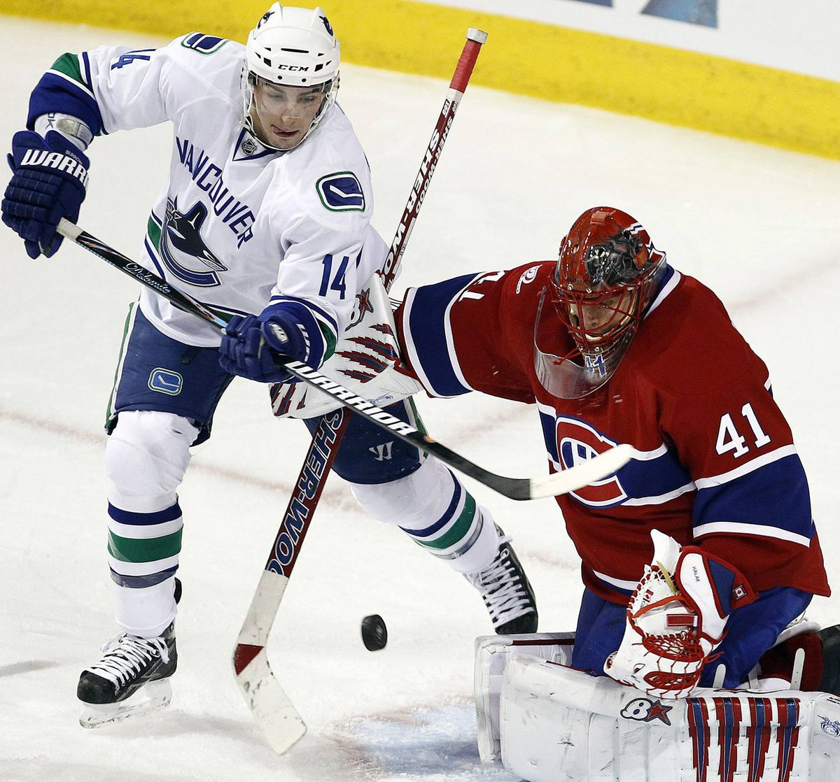 Montreal Canadiens goalie Jaroslav Halak (41) makes a save on Vancouver Canucks Alex Burrows (14) during third period NHL hockey action in Montreal, February 2, 2010. REUTERS/Christinne Muschi