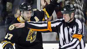 Referee Kevin Pollock, right, signals as Boston Bruins' Patrice Bergeron (37) celebrates after making the winning goal in a shootout against the Nashville Predators during an NHL hockey game in Boston, Saturday, Feb. 11, 2012. The Bruins won 4-3. (AP Photo/Michael Dwyer)