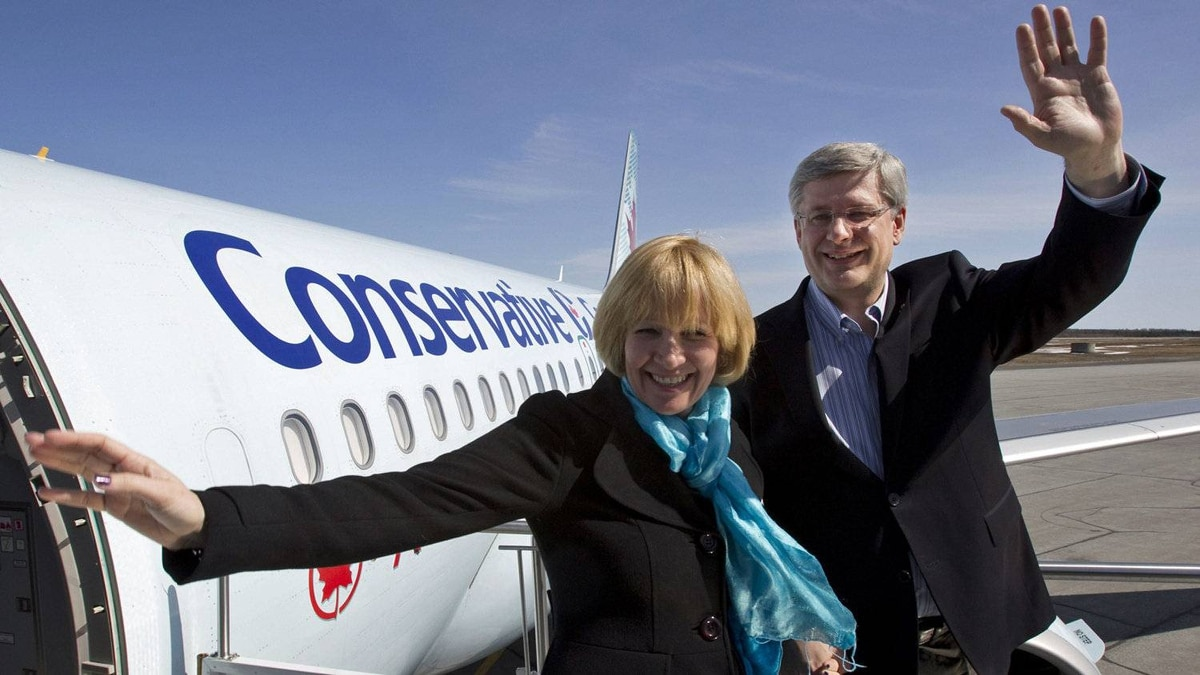 Conservative Leader Stephen Harper and his wife Laureen wave upon arrival in Val D'Or, Que., on April 19, 2011.