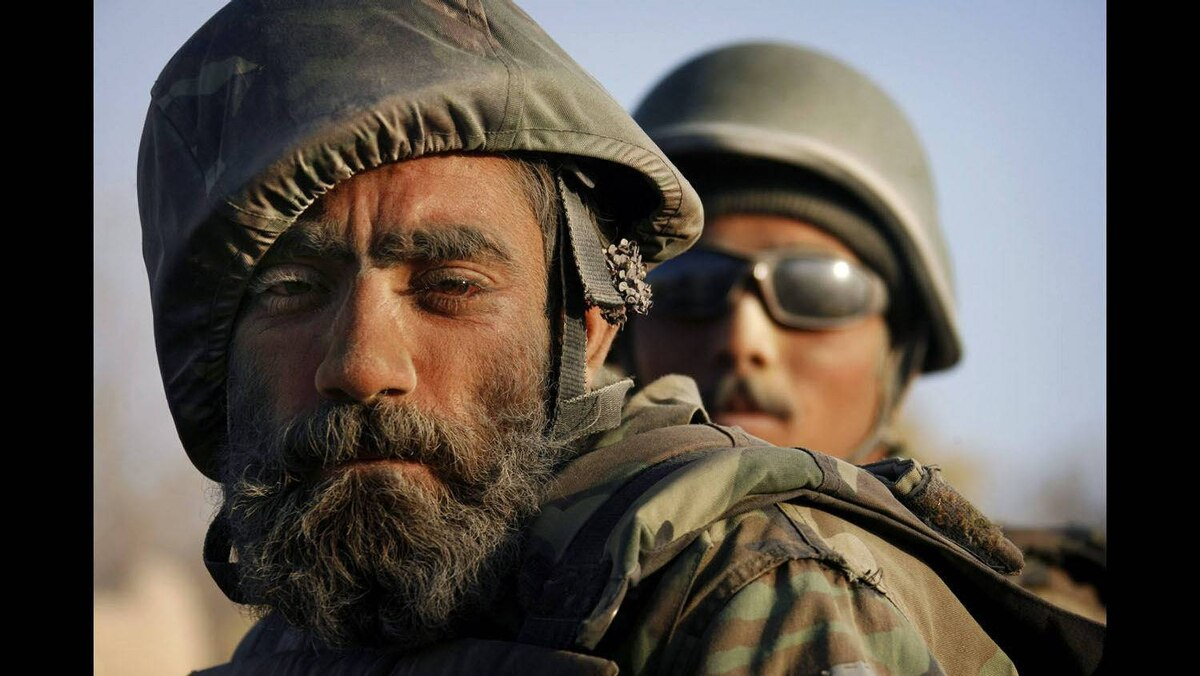 A dust-covered Afghan National Army soldier with a flower tucked behind his ear rides on the back of a vehicle during a patrol near the Taliban stronghold of Panjwaii town, Kandahar province, southern Afghanistan, November 13, 2007.