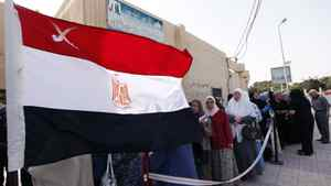 A national flag waves as Egyptians line up outside a polling station to cast their votes during the first day of the presidential elections in Alexandria, Egypt, Wednesday, May 23, 2012.