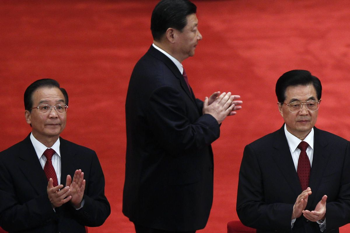 In this May 4, 2012 file photo, Chinese President Hu Jintao, right, Premier Wen Jiabao, left, and Vice President Xi Jinping, center, clap as they arrive for a conference to celebrate the 90th anniversary of the founding of the Chinese Communist Youth League at the Great Hall of the People in Beijing.