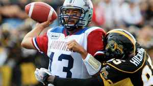 Montreal Alouettes quarterback Anthony Calvillo tries to throw a pass as he is hit by Hamitlon Tiger-Cats Justin Hickman during first-half. THE CANADIAN PRESS/Dave Chidley