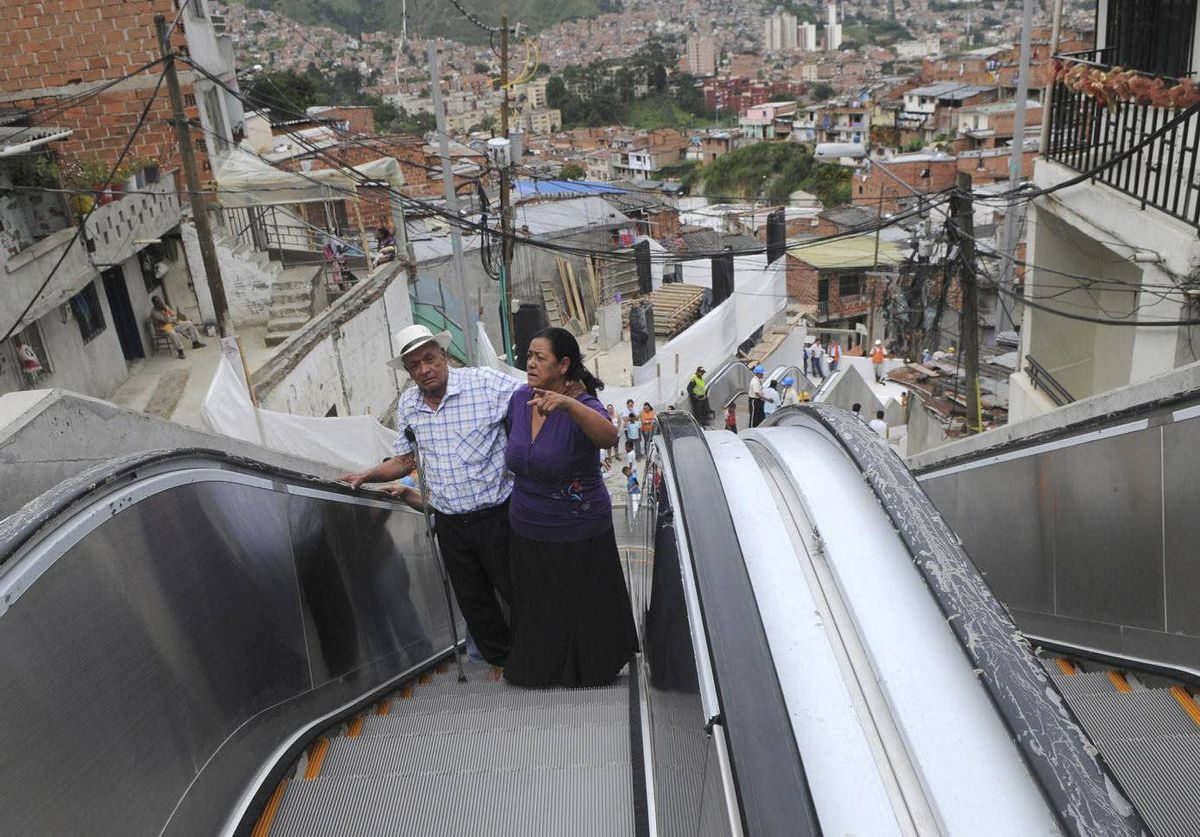 Luis Hernesto Holguin, left, and his sister Resfa Holguin use outdoor escalators, newly installed at Comuna 13 shantytown as part of an urbanization plan to improve living conditions of residents, in Medellin, Colombia. The improvement in Colombia's security situation is critical to its economic prospects.