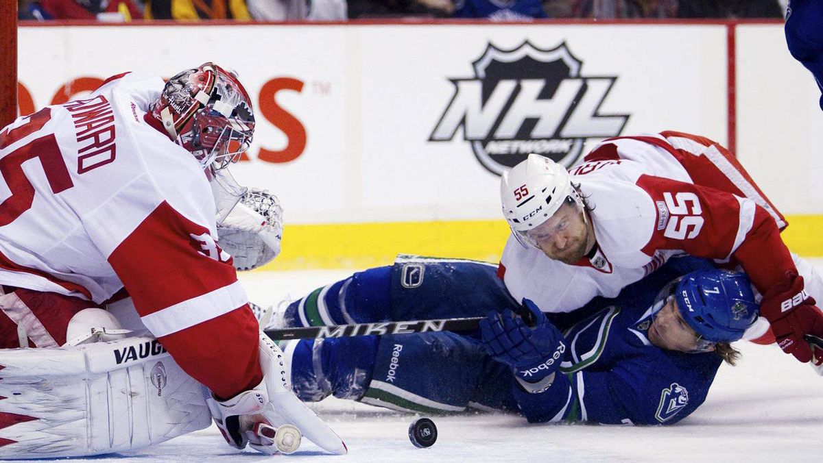 Vancouver Canucks' David Booth is knocked to the ice by Detroit Red Wings' Niklas Kronwall while trying to score on Red Wings goaltender Jimmy Howard during the first period of their game in Vancouver on Feb. 2, 2012.