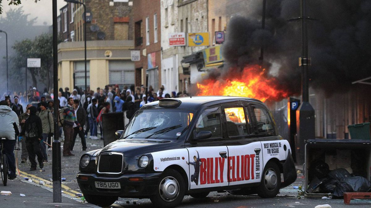 A car, behind the taxi, burns after it was set on fire by rioters in Hackney, east London, Monday Aug. 8, 2011.