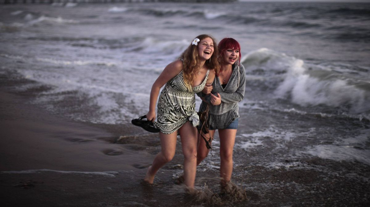 Women walk in the ocean in Santa Monica, California August 25, 2011. Temperatures were over 100 F in parts of Los Angeles County.