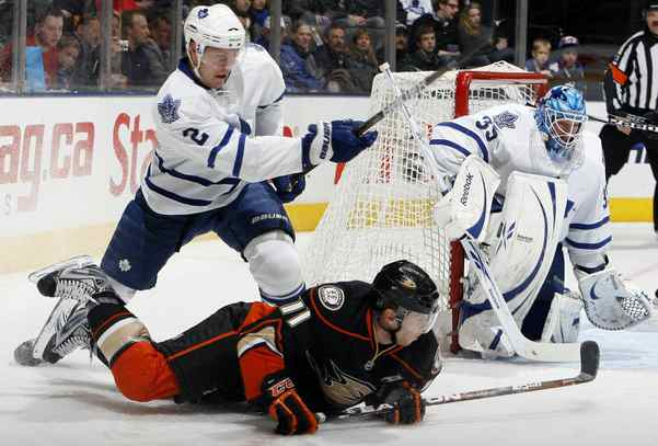 Luke Schenn of the Toronto Maple Leafs clears the puck past Saku Koivu of the Anaheim Ducks during game action at the Air Canada Centre January 20, 2011 in Toronto, Ontario, Canada.