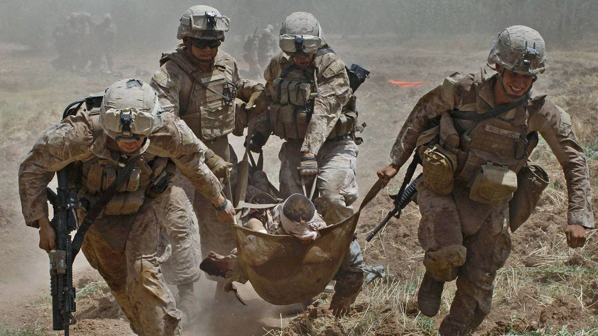 U.S. Marines carry a comrade wounded by an improvised explosive device (IED) to a waiting medevac helicopter, near the town of Marjah in Helmand Province, in this August 21, 2010 file photo.