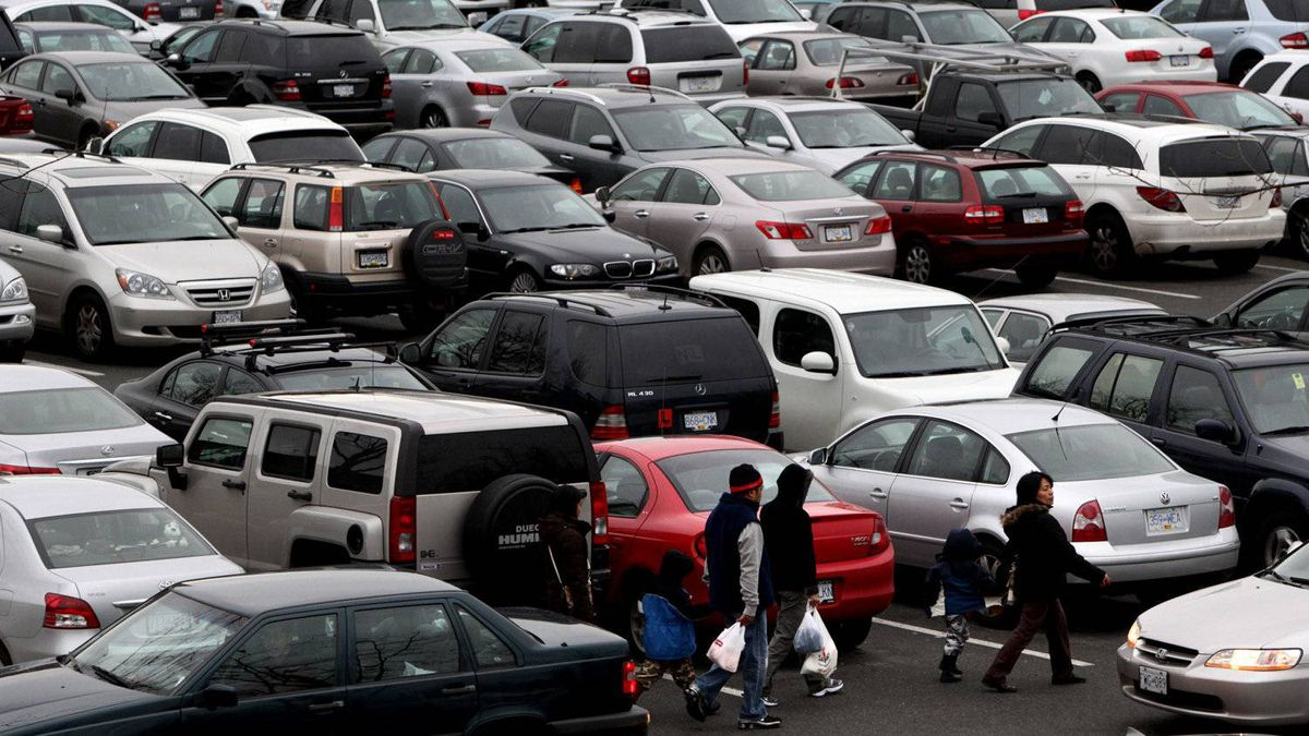 Shoppers walk past a sea of cars that fill a parking lot at Oakridge Centre mall in Vancouver.