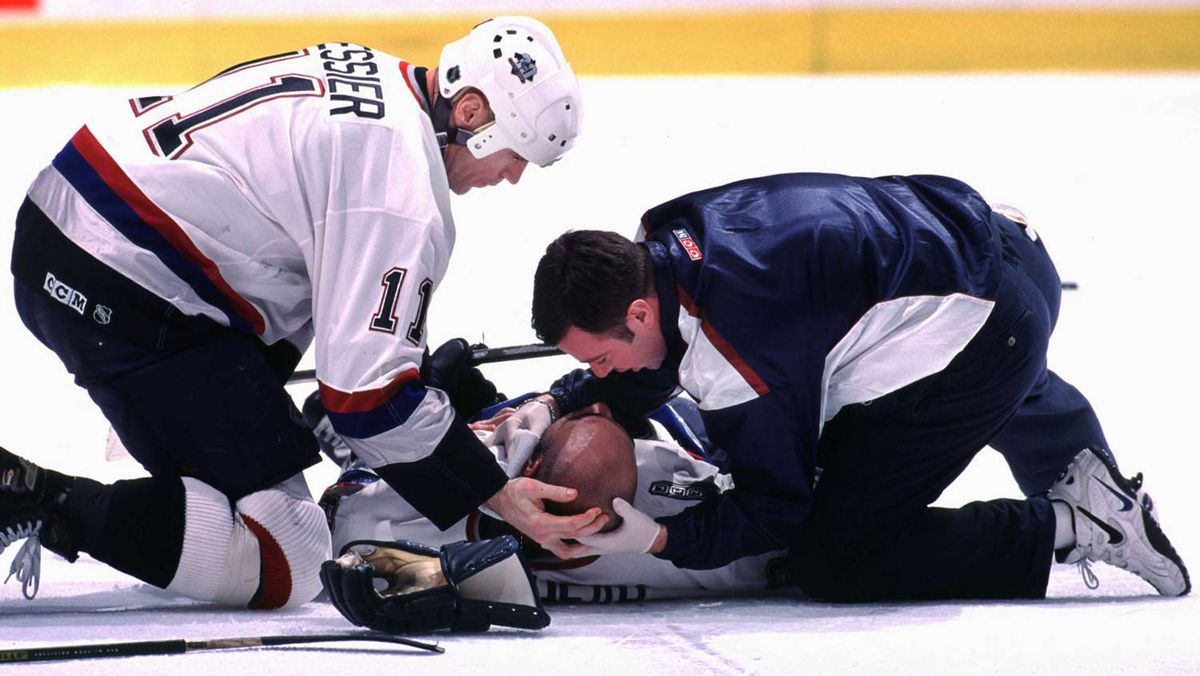 Vancouver Canuck captain Mark Messier and team trainer Mike Bernstein attend to Canuck's Donald Brashear on the ice during the third period of their game against the Boston Bruins February 22, 2000. Brashear was knocked to the ice unconscious after he was struck in the head by the stick of Bruin's Marty McSorley.