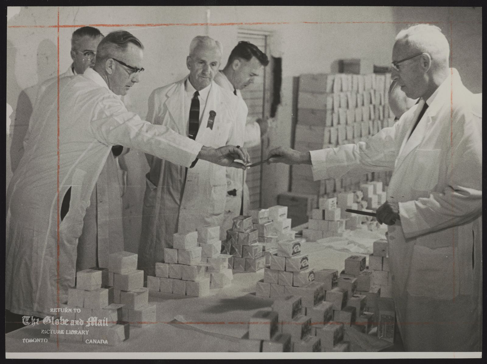 BUTTER Butter judges begin work at the Canadian National Exhibition. V. E. VanDeusen, head of Toronto dairy products division, Federal Department of Agriculture (left), takes butter sample from Robert Carleton, Saskatoon office (right). Onlookers are (from left) G. M. Borland, chief butter inspector in Ontario; Albert Baker, CNE dairy superintendent; Leslie Farquharson, Ontario Agriculture Department field man.