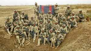 """Members of 2 Troop, 23 Field Squadron pose for a photograph at the conclusion of Operation Topak Shkar (""""Gun Hunter"""" in Pashto), a two-day airmobile operation in the Adamzai area of Panjwai District, with the aim of disrupting insurgent supply lines and finding arms caches. The flag is the standard of Canadian combat engineers. Sgt. Wadleigh is seated in front of it, on the right."""