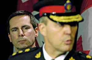 Ontario Premier Dalton McGuinty looks on as Toronto Police Chief Bill Blair speaks during a news conference on January 5, 2006.