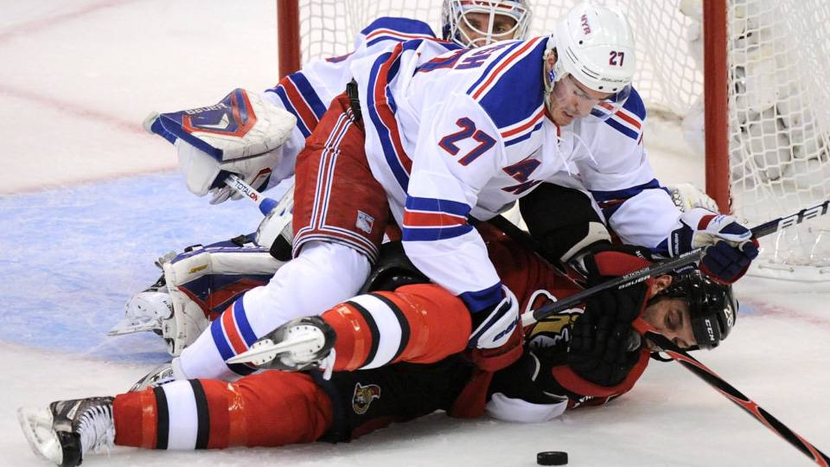 Ottawa Senators' Zenon Konopka keeps his eye on the puck as he gets hit to the ice by New York Rangers' Ryan McDonagh as goalie Henrik Lundqvist looks on during the first period of Game 3 of first round NHL Stanley Cup playoff hockey action at the Scotiabank Place in Ottawa on Monday.