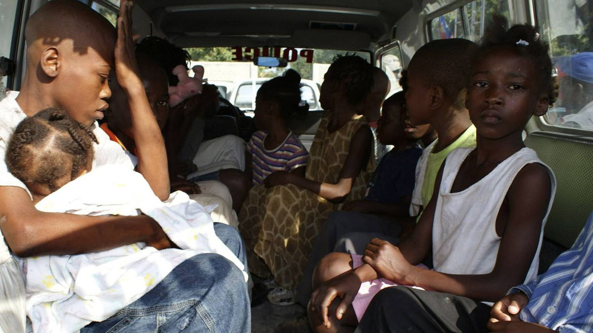 Children suspected of being involved in an illicit adoption scheme sit in a local police car in Port-au-Prince January 30, 2010. Haitian police have arrested 10 U.S. citizens caught trying to take 33 children out of the earthquake-stricken country in a suspected illicit adoption scheme, authorities said on Saturday. (Guy Delva/Reuters)