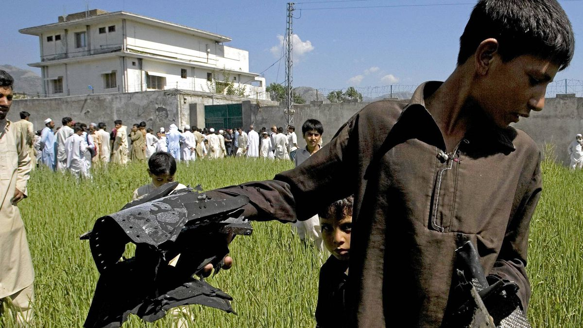 A Pakistani youngster shows metal pieces collected from wheat field outside a house, seen background, where al-Qaeda leader Osama bin Laden lived in Abbottabad, Pakistan, May 3, 2011.