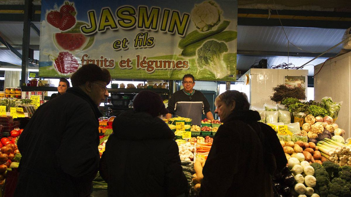 Shoppers browse the vegetable stand at Luc Jasmin's shop in Atwater Market.