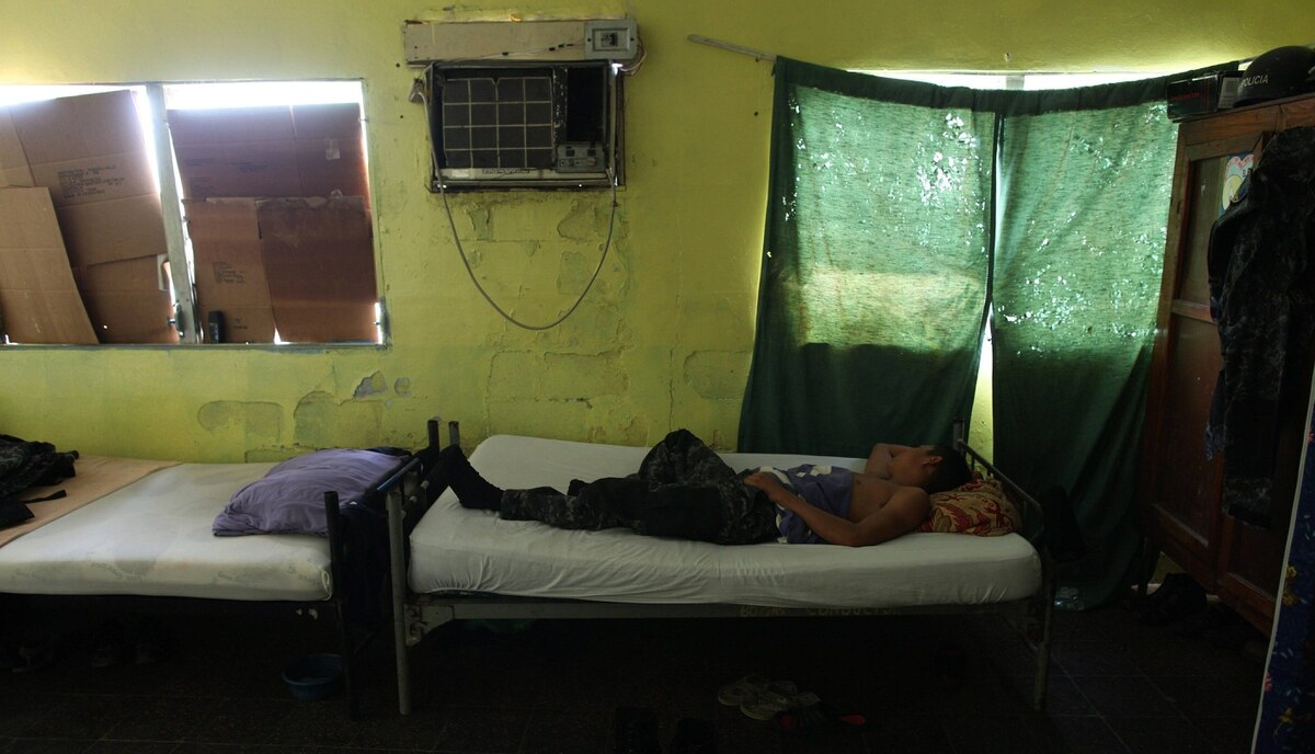 A member of the Cobras elite police force, part of the national police, rests in a bedroom at their headquarters in San Pedro Sula, Honduras, March 8, 2012. The city's location near Honduras' Atlantic coast and border with Guatemala have put it on key international drug trafficking routes.