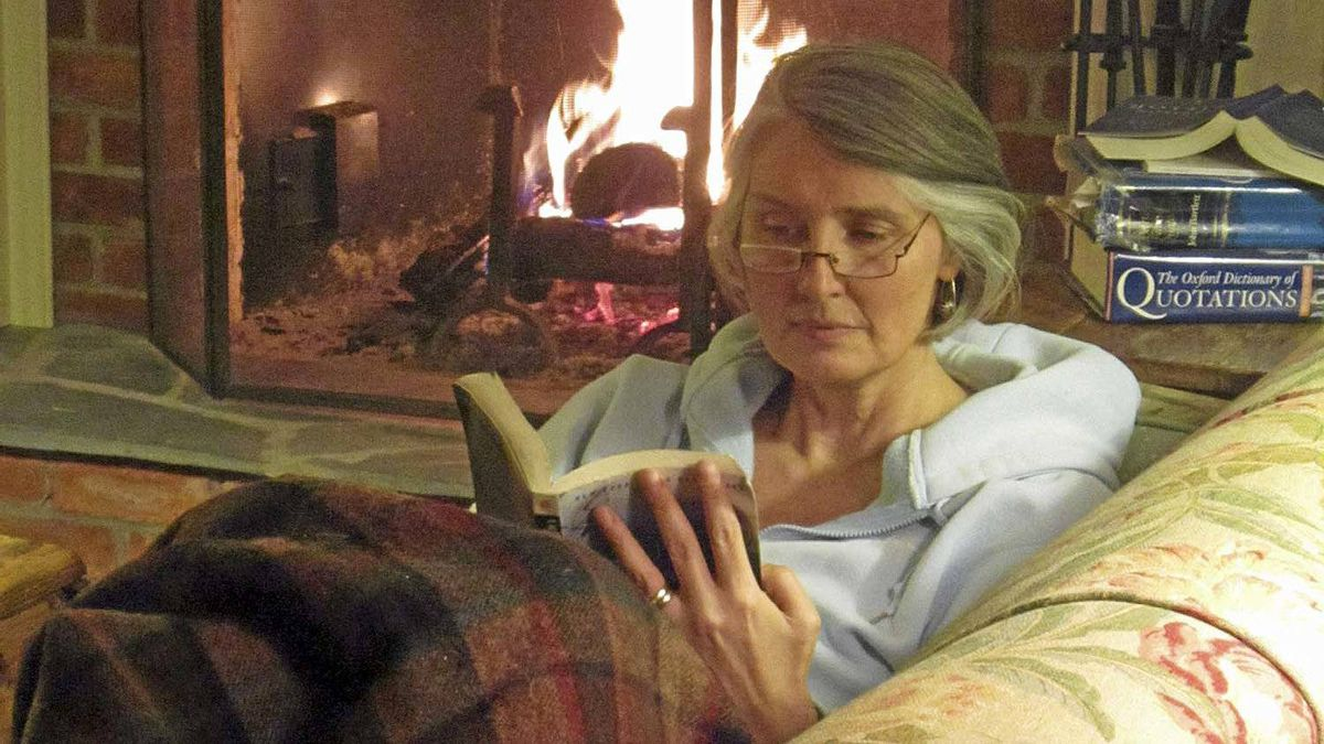 Louise Penny reading by the fire.