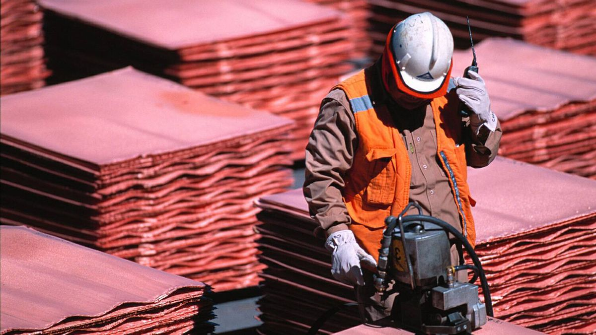 An employeee at the BHP Billiton copper mine at Escondida works amid sheets of copper.