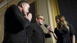 Sir Elton John, centre, and husband David Furnish are interviewed by a TV presenter as they arrive at the opening night of 'Billy Elliot the Musical' in Toronto on March 1, 2011.
