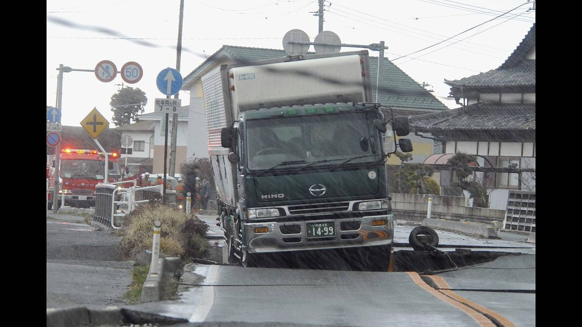 A truck remains stranded on a road damaged by a powerful earthquake in Iwaki city, Fukushima prefecture (state), Japan, Friday, March 11, 2011.
