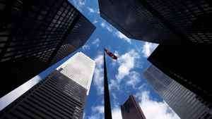 Skyscrapers loom over a flagpole carrying the Canadian flag in the financial district in Toronto, March 11, 2009.