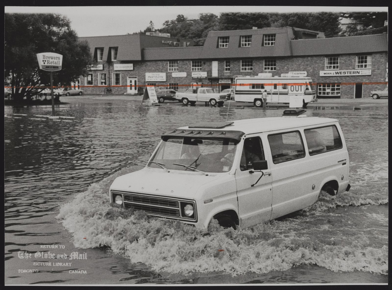 FLOODS Canada Van is crossing parking lot at shopping plaza in Huntsville.