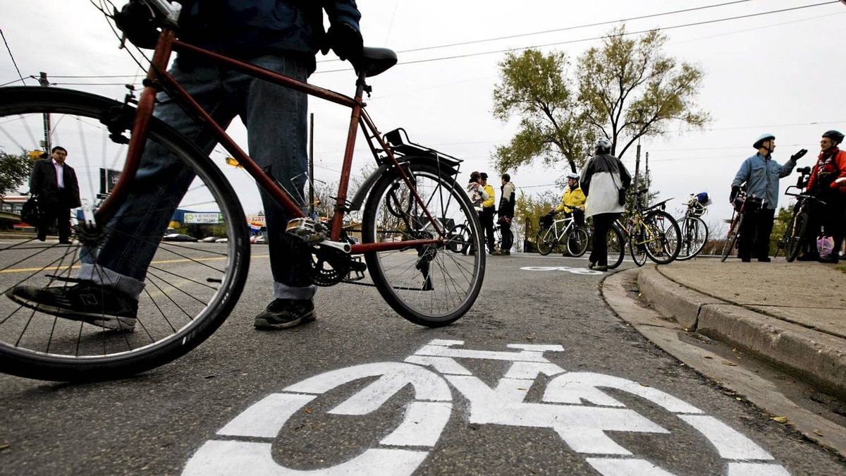 A cyclists walks by a bike lane symbol painted by activists at a memorial on Monday, November 14, for pregnant cyclist Jenna Morrison, who was killed after being struck by a truck at Sterling and Dundas in Toronto.