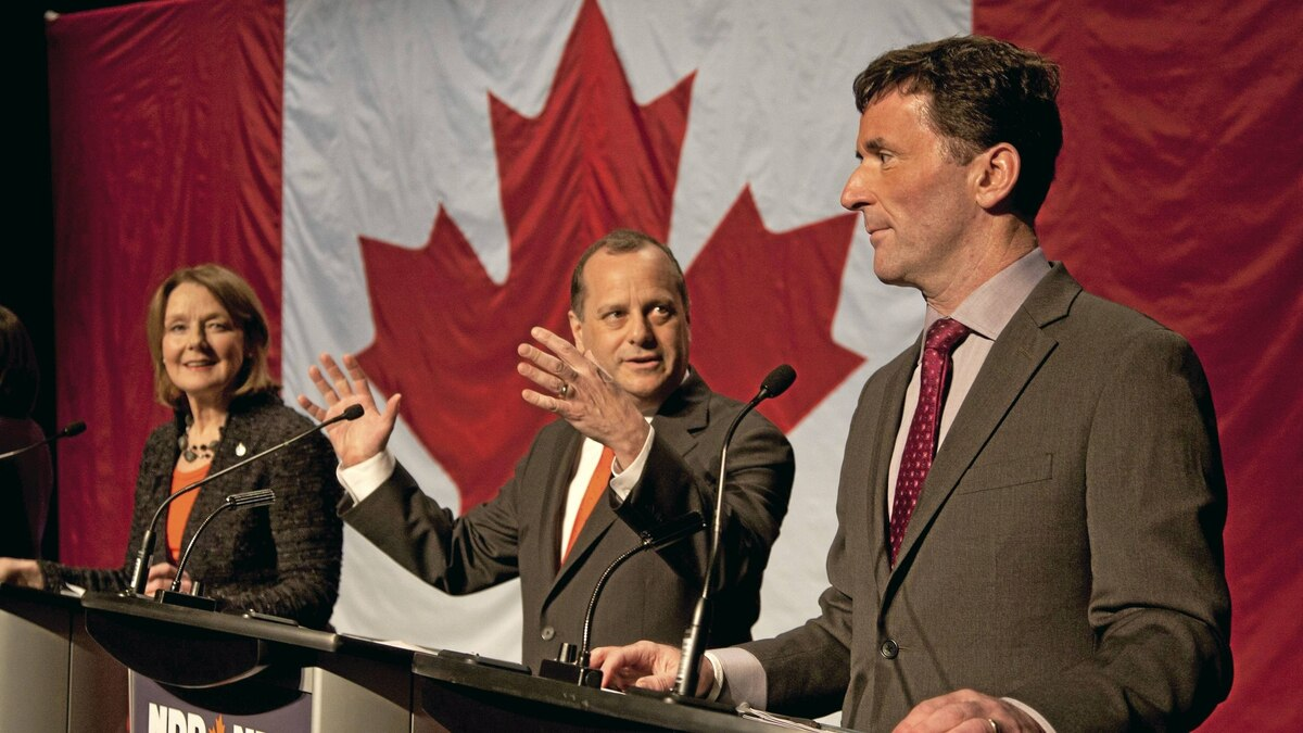 NDP federal leadership candidate Brian Topp gestures prior to the start of a leadership debate in Halifax as fellow candidates Peggy Nash and Paul Dewar look on Jan. 29, 2012.