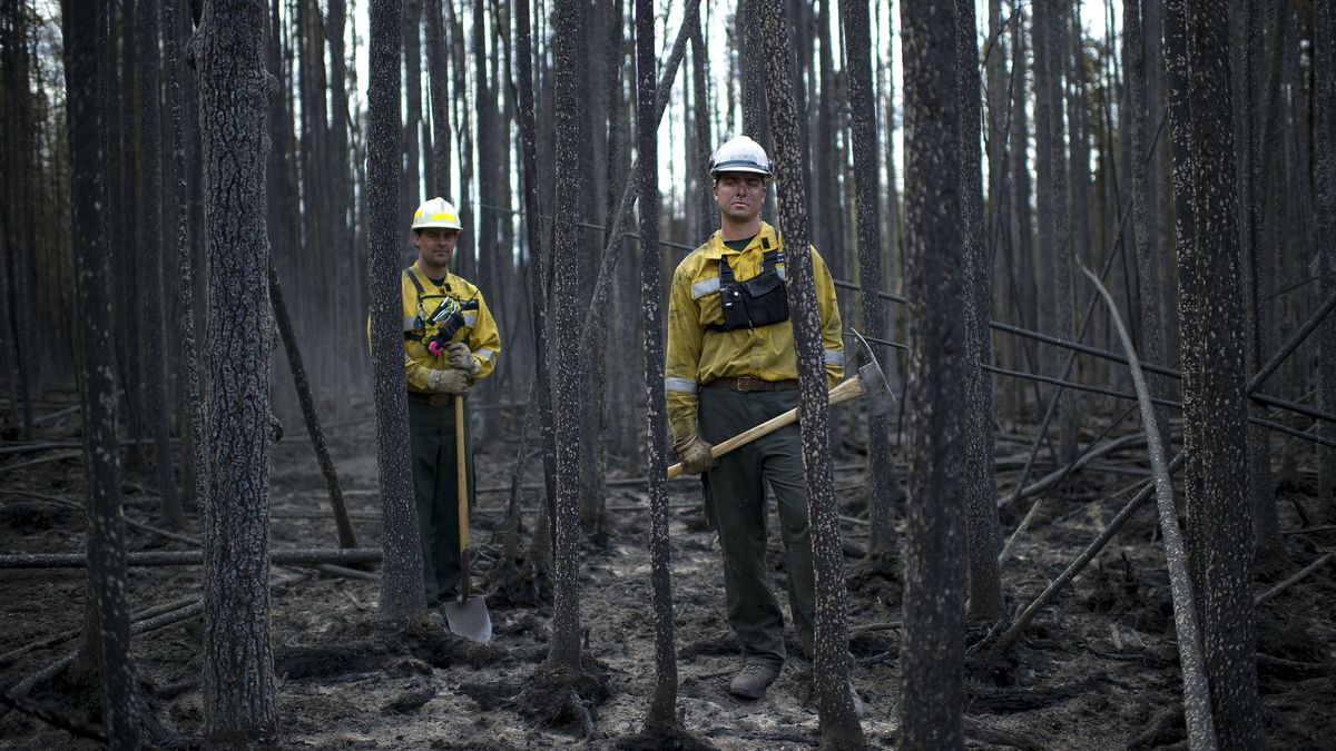 Wildfire Rangers with Alberta Sustainable Resource Development Troy Johanson and Jason McAleenan, part of a strike team, put out hot-spots near the site of the point of origin for the fire around Slave Lake, Alberta on May 19, 2011.