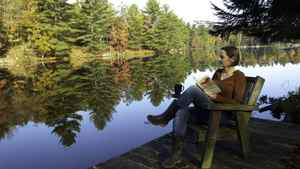 Barbara Reid reads on the canoe dock at her family cottage on Ontario's Severn River.