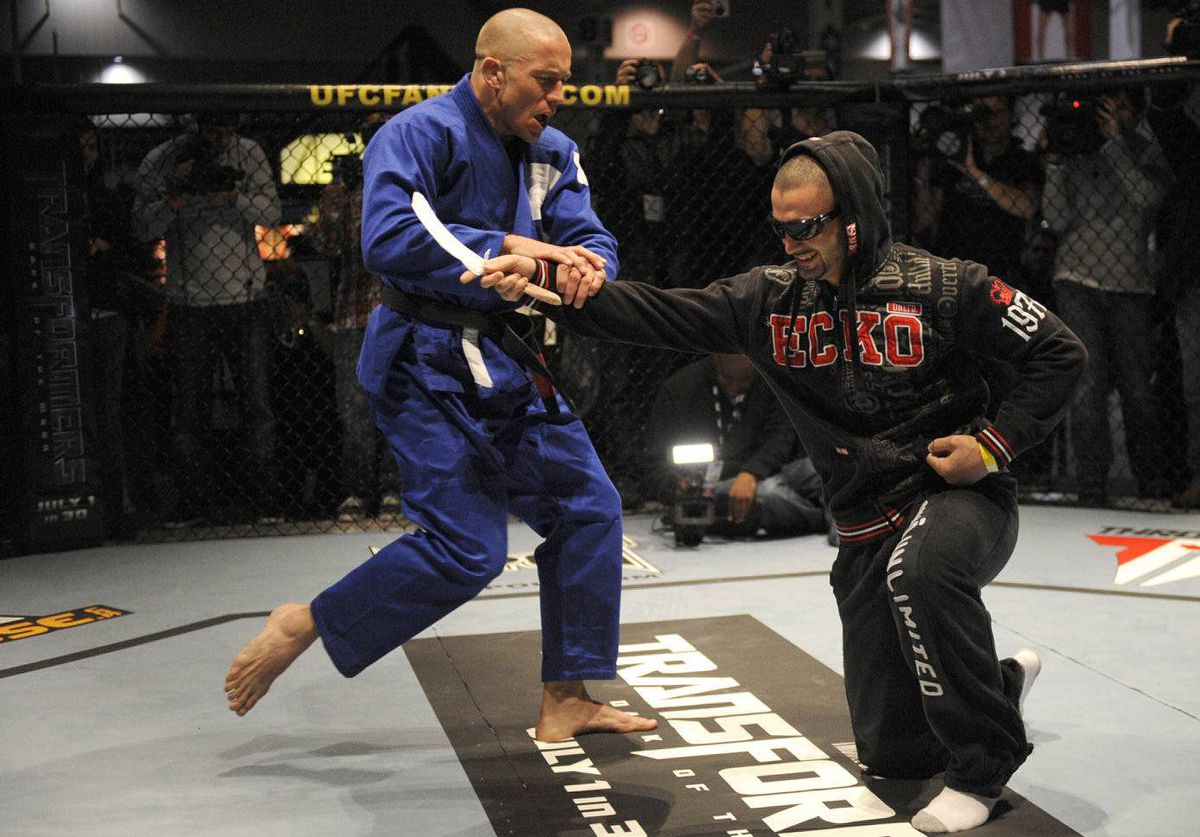 UFC welterweight champion Georges St-Pierre, left, defends himself against an attacker in a staged scenario during an open workout at the Direct Energy Centre in Toronto.